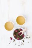 Groene thee met rosebuds en koppen op een witte lijst, hoogste mening Royalty-vrije Stock Afbeelding