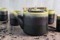 Groene thee in theepot met kleine koppen over, houten achtergrond Royalty-vrije Stock Afbeelding