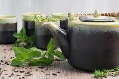 Groene thee in theepot met kleine koppen over met munt, houten achtergrond Stock Foto's