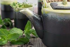Groene thee in theepot met kleine koppen over met munt, houten achtergrond Royalty-vrije Stock Afbeeldingen