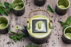 Groene thee in theepot met kleine koppen over met munt, houten achtergrond Stock Afbeeldingen
