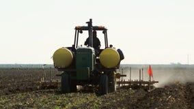 Groene tractor die het tarwegebied bespuiten stock footage