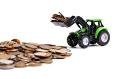 Groene tractor die omhoog muntstukken harkt royalty-vrije stock afbeeldingen