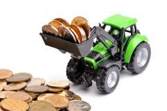 Groene tractor die omhoog muntstukken harkt stock afbeeldingen