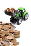 Groene tractor die omhoog muntstukken harkt royalty-vrije stock afbeelding