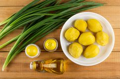 Groene ui, zout, peper, fles met plantaardige olie, aardappelen in de schil in plaat op houten lijst Hoogste mening royalty-vrije stock afbeeldingen