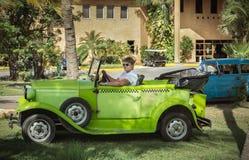 Groene uitstekende klassieke auto met een jonge taxibestuurder bij Cubaanse tropische tuin Stock Afbeeldingen