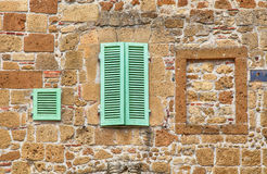 Groene vensterblinden op oude steen geweven muur, Italië Stock Fotografie