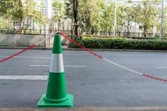 Groene verkeerskegel met rode en witte kettingen voor parkeren stock afbeeldingen