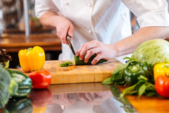 Groene verse komkommerbesnoeiing door handen van professionele chef-kokkok Stock Foto's