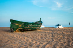 Groene vissersboot op het strand en de blauwe hemel Stock Foto