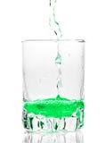 Groene vloeistof die in een transparant glas wordt gegoten royalty-vrije stock foto