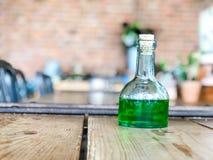 Groene vloeistof in Glasflessen op houten lijst bij koffie, drank het drinken stock foto