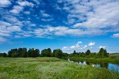 Groene weide en rivier, zonnige dag Royalty-vrije Stock Foto's