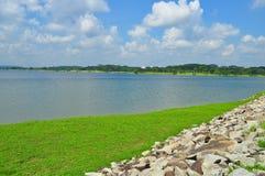 Groene weiland en stenen door een reservoir Royalty-vrije Stock Afbeelding