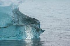 Groenland, blauwe duidelijke ijsberg in het water bij het strand royalty-vrije stock foto's