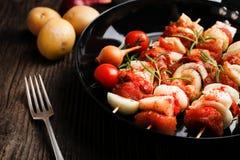 Groente en vlees op houten vleespennen op plaat Stock Fotografie