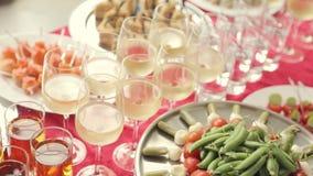 Groenten, desserts, snacks, canapes, alcohol en water in de koppen bij het banket over catering stock videobeelden