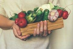Groenten in een houten doos in de handen stock fotografie