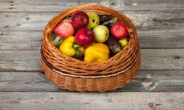 Groenten en appelen in mand op oude houten lijst Stock Afbeelding
