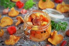Groenten en paddestoelencantharellen in een glaskruik Stock Fotografie