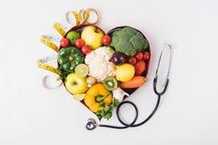 groenten en vruchten die in hart gevormde schotel dichtbij stethoscoop leggen en band meten stock foto's
