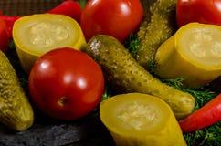 Groenten in het zuur: komkommertomaten, courgette en kruiden op een houten achtergrond worden verspreid die Royalty-vrije Stock Fotografie