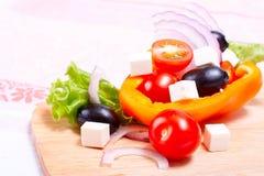 Groenten, kaas en olijven op het keukenbord Stock Foto's