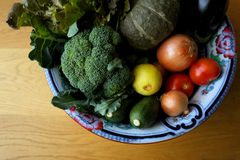 Groenten met inbegrip van Broccoli, Pompoen, Uien, Tomaten, Courgettes, Aubergines, Sla, Citroenen in Kom op een Houten Achtergro royalty-vrije stock foto's
