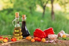 Groenten met olie op houten lijst Stock Afbeeldingen