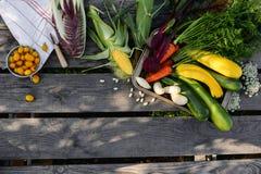 Groenten op de lijst Verse wortelen, tomaat, ui en greens op de natte houten lijst Royalty-vrije Stock Foto's