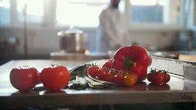 Groenten, tomaten die, paprika, preien op de lijst en de pot liggen die zich op de brand bevinden in de commerciële keuken stock footage