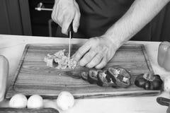 Groenten worden die die op houten scherpe raad worden gesneden De groene salade van de handplak met ceramisch mes De groenten van stock foto's