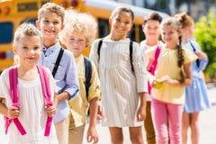 groep aanbiddelijke schoolkinderen die zich in rij voor school bus en het kijken bevinden stock afbeeldingen