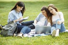 Groep aantrekkelijke jongeren die voor het examen met studieboek en een laptop zitting op het gazon voorbereidingen treffen Stude royalty-vrije stock foto