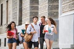 Groep aantrekkelijke tienerstudenten die aan universiteit lopen Stock Foto's