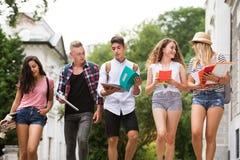 Groep aantrekkelijke tienerstudenten die aan universiteit lopen Stock Fotografie
