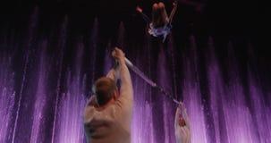 Groep acrobaten die handeling met pool tegen kleurrijke fonteinen, Moskou, Rusland maken