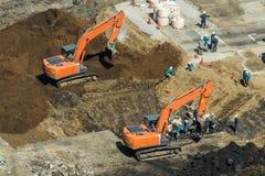 Groep arbeiders die aan bouwwerf met graafwerktuigen werken Stock Fotografie