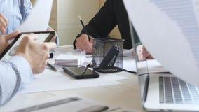 Groep arbeiders die bij lijst in bureau zitten en efficiënt met documenten werken Handen van zakenlieden van creatief stock footage