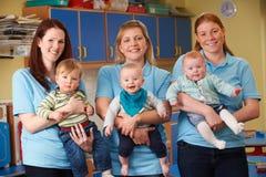 Groep Arbeiders met Babys in Kinderdagverblijf Stock Foto's