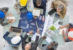 Groep Architecten die met Blauwdruk plannen Stock Foto