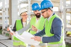 Groep architecten of partners die vergadering over een bouwwerf hebben stock afbeelding
