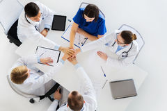 Groep artsen die handen houden samen bij lijst Stock Fotografie