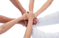 Groep artsen die handen samen stapelen Stock Foto's