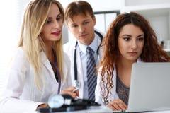 Groep artsen die laptop de zitting van PC in bureau gebruiken stock fotografie