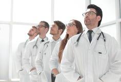 Groep artsen die zich op een rij en een exemplaarruimte bevinden bekijken Royalty-vrije Stock Afbeelding
