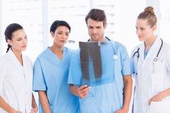 Groep artsen en chirurgen die röntgenstraal onderzoeken stock foto's