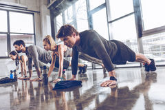Groep atletische jongeren in sportkleding die duw UPS of plank doen bij de gymnastiek royalty-vrije stock afbeeldingen