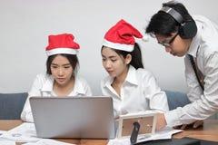 Groep Aziatische bedrijfsmensen met de hoed die van de Kerstman in werkplaats van bureau samenwerken stock afbeeldingen